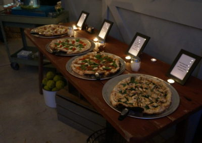 Pizzas with placards on a candle lit table for a catered event.