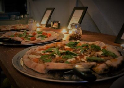 Catered Pizzas out on a display table with name placards and candles
